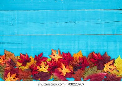 Colorful fall leaves border with blank antique rustic teal blue wood background; autumn, Thanksgiving, Halloween, seasonal nature sign with painted wooden copy space