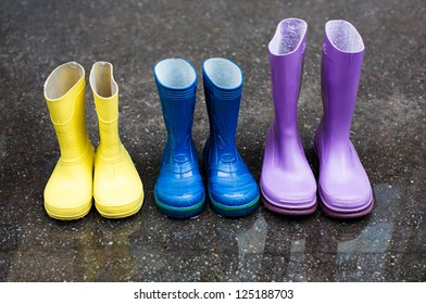 Colorful family boots at rainy day on street