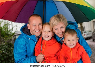 colorful family smiling in the rainy day under umbrella