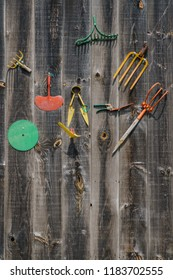 Colorful farm tools on side of gray barn