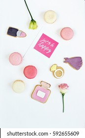 Colorful feminini flat lay of rose, card and pink, violet cookies in the fashion style. Top view. Text Just to be happy.