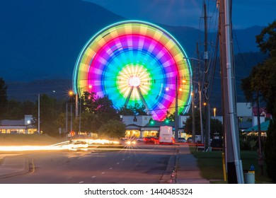 A colorful ferris wheel along a busy street.