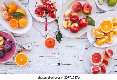 Colorful festive assortment of purple, red and orange fruit background in bowls. Lime, pomegranate, tangerine, orange, mandarin, apple, plum, grapefruit, lime sliced above white rustic tabletop.