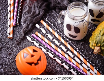 Colorful festive striped paper straws and Halloween decor. Selective focus