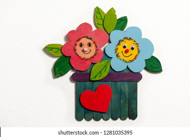 Colorful figure of flowers in a garden made of wood by a child, white background