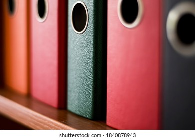 Colorful files on a shelf to assort the documents in the office. Red, orange and green plastic folders.