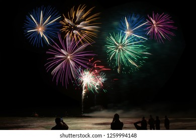 Colorful firework explosions above the sea