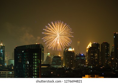 Colorful firework on sky at night over the skyscraper in downtown Bangkok, the capital city of Thailand in southeast Asia, in horizontal view.