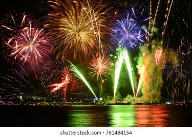 Colorful fireworks celebration and the city night light background.