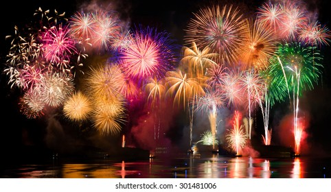 Colorful fireworks. Fireworks are a class of explosive pyrotechnic devices used for aesthetic and entertainment purposes. Visible noise due to low light, soft focus, shallow DOF, slight motion blur