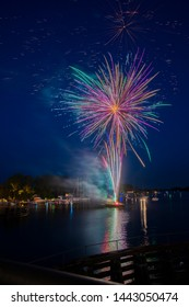 Colorful fireworks launched from a barge and reflected in the water.