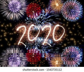 Colorful fireworks in the night sky with reflect in water and sparkling 2020 text