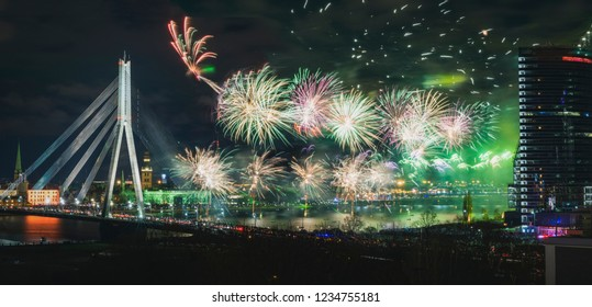 Colorful fireworks over river Daugava on Latvia's 100th birthday. Independence day celebration in Riga city with panoramic view over the old town and cable bridge. Light show in Riga city.
