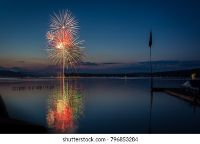 Colorful fireworks reflecting in a lake.