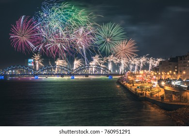 Colorful fireworks in Riga city with panoramic view over the river Daugava and railroad bridge. New year celebration. (NOT A PAINTING)