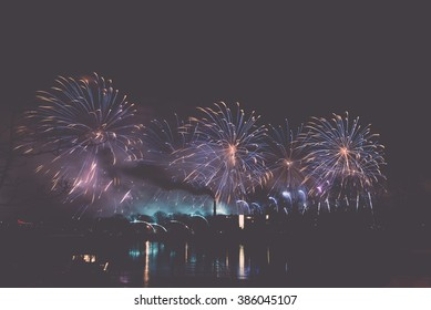 Colorful fireworks of various colors over night sky - vintage effect