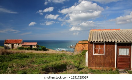 Colorful Fisherman's huts on Alentejo West Coast with dramatic cliffs in the background, Porto das Barcas, Zambujeira do Mar, Alentejo, Portugal