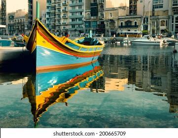 Colorful fishermen's boat reflected in water in St. Julian's Bay, Malta