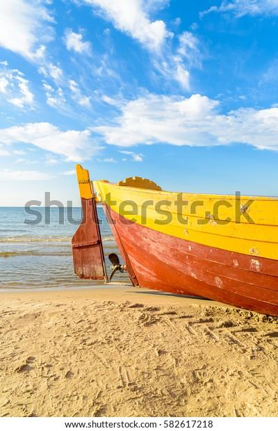Colorful fishing boat on sandy Debki beach during sunny summer day, Baltic Sea, Poland