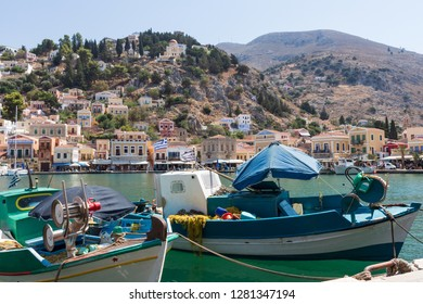 colorful fishing boat with the skyline of Symi in the background