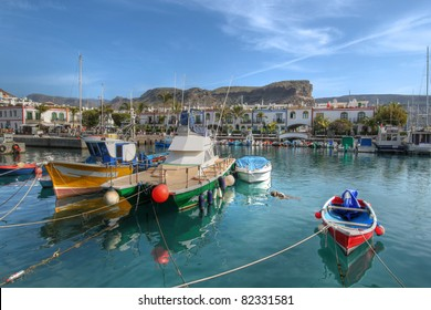 Colorful fishing boats moored in the small marina of Puerto de Mogan on the south coast of Gran Canaria Island, Spain.