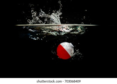 A colorful fishing bobber splashes in the water
