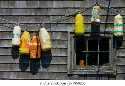 Colorful fishing floats hanging on the side of an old shed in Peggy's Cove Nova Scotia