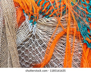 Colorful fishing nets are drying on the quay in the harbor next to the fish auction