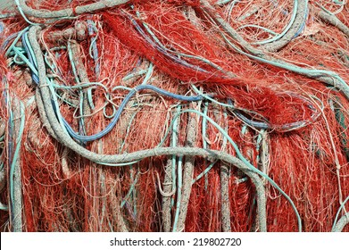 Colorful fishing nets in tangled heap on quay, suggesting chaos and confusion; Ajjacio, Corsica. In Eastern thought, nets represent the interlocking aspects of life; this life is complex.