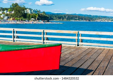 Colorful fishing rowboat on old wooden wharf. Coastal view with with busy beach