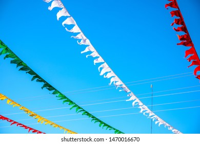 Colorful flag ribbons in sunny blue sky. Festival flag decor. Summer day outdoor. Optimistic skyscape with triangle ribbon. Flag banner stretched over road. Decorative ribbon banner in sunny sky