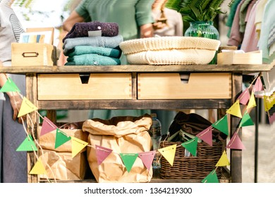 Colorful flags, craft paper bags and goods for garage sale on the summer vintage festival market