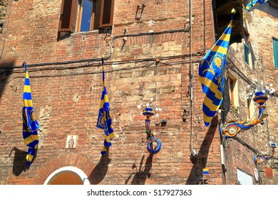 Colorful flags and lamps decorating medieval streets in Siena during Palio, Tuscany, Italy