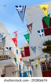 Colorful flags at narrow street of typical greek traditional village with white walls and colorful doors, windows and balconies on Mykonos Island, Greece, Europe