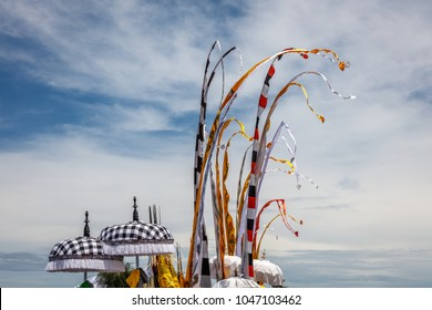 Colorful flags on the beach during Melasti, Hindu ceremony of purification before Nyepi. Pantai Seseh, Bali, Indonesia.