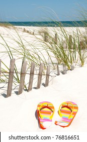 colorful flip flops on sand dune