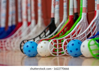 Colorful Floorball Sticks & Balls Lined Up Along a Wood Court