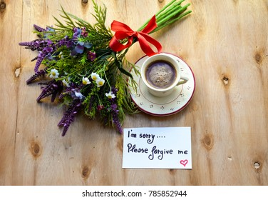 Colorful flower bouquet and i'am sorry please forgive me text on a note and a coffee cup on rustic wooden table