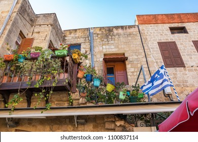 Colorful flower pots in narrow streets of old town in City of Rhodes (Rhodes, Greece)