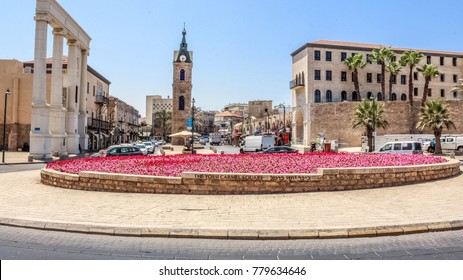 Colorful flowerbed on Yossi Carmel Square, Jaffa Clock Tower on the background, Old Jaffa, Israel