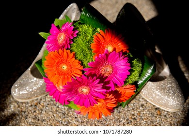 colorful flowers for the bride to the wedding. bouquet with gerbera pink orange green and grass in front of sparkling high heels