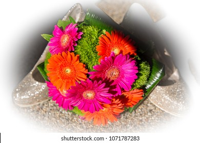 colorful flowers for the bride to the wedding. bouquet with gerbera pink orange green and grass in front of sparkling high heels with silhouette