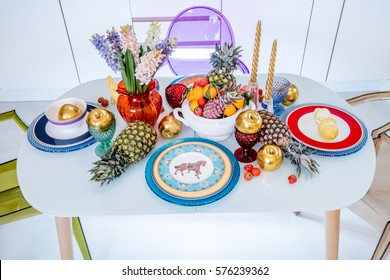 Colorful flowers, fruits and dishes, bright look set table.