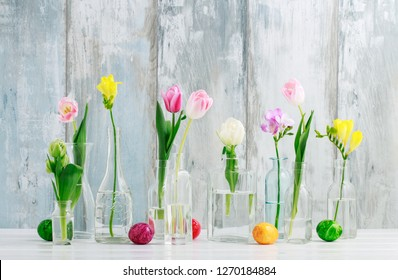 Colorful flowers in glass bottles and Easter eggs on the table. Greetings background, copy space.