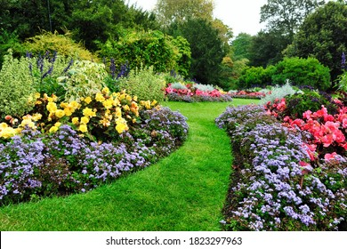 Colorful Flowers, Grass Lawn and Green Leafy Trees in a Beautiful English Style Garden