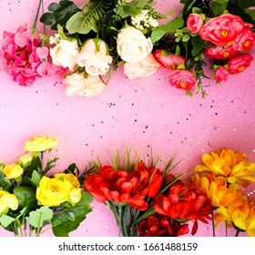 Colorful flowers on a pink background, confetti. Place for text. Festive background. Event. The concept. Flat lay. Top view.