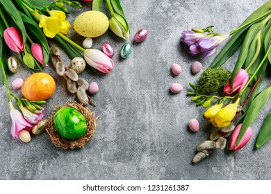 Colorful flowers and painted Easter eggs on grey, stone background. Copy space.