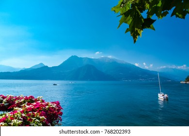 Colorful flowers terrace in front of beautiful scene of lake Como in Italy. A big blue lake surrounded by green hill.It is a famous travel destination for tourism. Tourist can sight seeing by yacht.