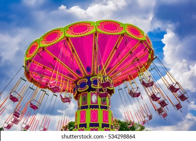 Colorful flying swing ride in motion at the amusement park
