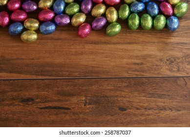 Colorful foil wrapped Easter egg shaped chocolate candy on a wood plank background with extra room for your text and images.